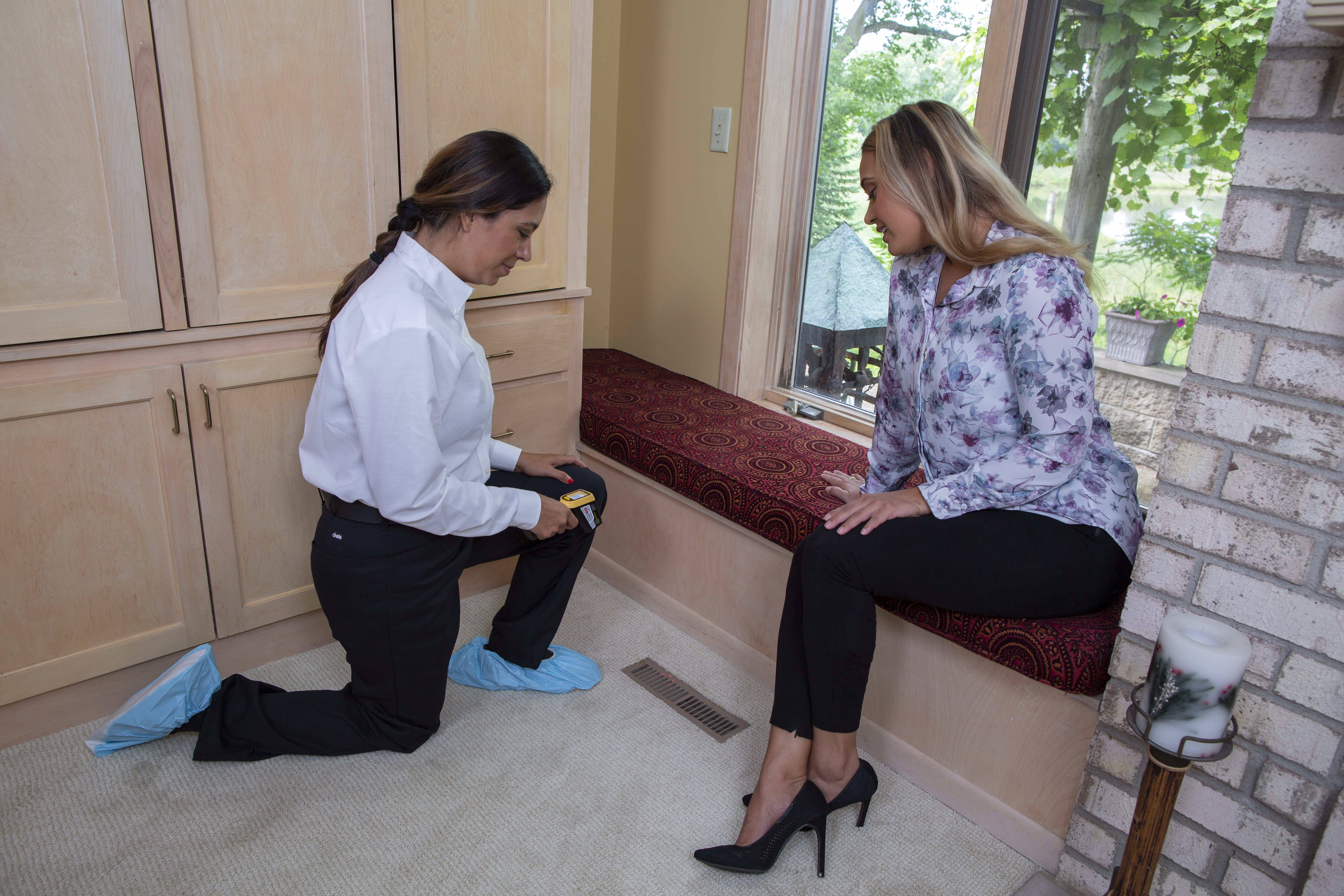 A female ACE technician kneeling holding an infrared thermometer near a vent  with a customer nearby
